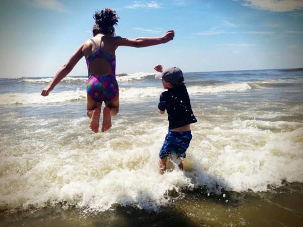 Beach kids jumping waves