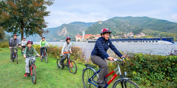 adventures-by-disney-europe-danube-river-cruise-itinerary-hero-01-biking-next-to-the-danube-river